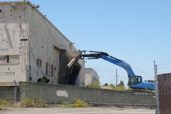 Demolition begins on WWII era buildings in 2012, to make way for Alameda Landing. (File Photo)